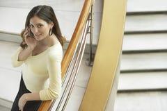 使用手机的女实业家,当倾斜在用栏杆围Stairc时 库存图片