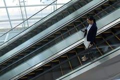 使用手机的女实业家,当移动下来在自动扶梯时 免版税库存图片