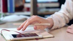 使用手机的女性手为在办公室工作场所计算赢利 股票录像