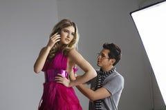 使用手机的女性时装模特儿,当调整她的礼服的设计师在演播室时 免版税库存图片