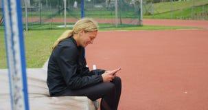 使用手机的女运动员在运动会比赛地点4k 影视素材