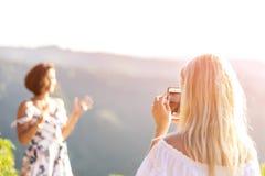 使用手机的妇女和为她微笑照相卷曲 库存图片