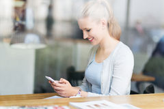 使用手机的妇女在咖啡馆 库存照片