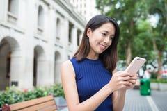 使用手机的妇女在室外 免版税库存图片