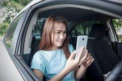 使用手机的妇女在汽车 免版税库存图片