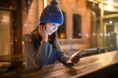 使用手机的妇女在酒吧柜台在咖啡店在晚上 库存图片