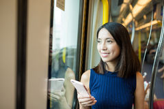 使用手机的妇女在香港的地铁隔间 免版税库存照片