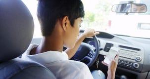 使用手机的妇女,当停放在汽车时 免版税图库摄影