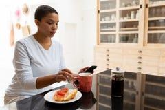 使用手机的妇女,当食用在饭桌时的咖啡 免版税库存图片