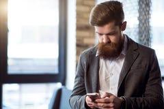 使用手机的宜人的残酷有胡子的人 免版税库存照片