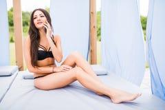 使用手机的小姐佩带的比基尼泳装,当晒日光浴由水池时 女性式样基于使用巧妙的电话的一deckchair 库存图片