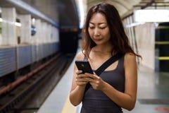 使用手机的年轻亚裔妇女在火车站 免版税库存图片