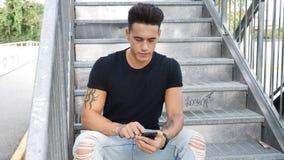 使用手机的年轻人户外在城市布局 库存照片