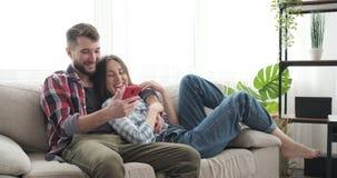 使用手机的年轻夫妇在沙发在家 股票录像