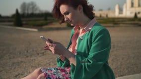 使用手机的年轻女人为测试和消息-在宫殿前面的喷泉-时尚高尔夫球外套 影视素材