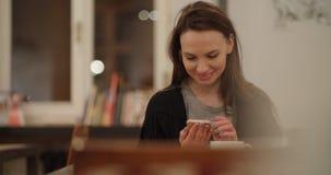使用手机的年轻快乐的妇女在餐馆 免版税图库摄影