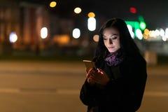 使用手机的年轻深色的妇女在晚上 库存图片