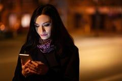 使用手机的年轻深色的妇女在晚上 免版税库存图片