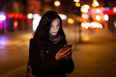 使用手机的年轻深色的妇女在晚上 免版税库存照片