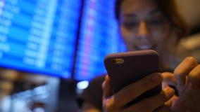使用手机的年轻混合的族种旅游女孩在离开委员会附近在机场 4K 曼谷泰国 股票视频