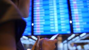 使用手机的年轻混合的族种旅游女孩在离开委员会附近在机场 4K 曼谷泰国 股票录像