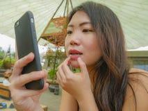 使用手机的年轻美丽和愉快的亚裔韩国妇女作为检查她的镜子做享用放松户外在甜点 免版税库存图片