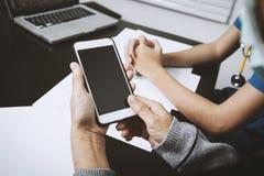 使用手机的年长妇女,当与护士协商时 免版税库存照片