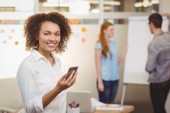 使用手机的微笑的女实业家 免版税库存照片