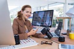 使用手机的微笑的女性执行委员,当拿着数字照相机在办公室时 库存图片