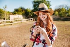 使用手机的微笑的女牛仔,当站立在大农场篱芭时 图库摄影