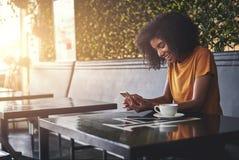 使用手机的微笑的年轻女人在咖啡馆 免版税图库摄影