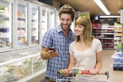 使用手机的快乐的年轻夫妇在超级市场 免版税库存图片