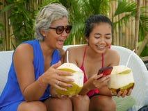 使用手机的愉快和美丽的亚裔印度尼西亚少年女孩享受喝椰子的夏天休假在热带手段 免版税库存照片