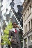 使用手机的愉快的商人在大厦之外 免版税图库摄影
