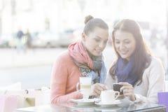 使用手机的愉快的妇女在边路咖啡馆在冬天期间 免版税库存照片