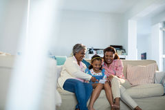 使用手机的愉快的家庭在客厅 图库摄影