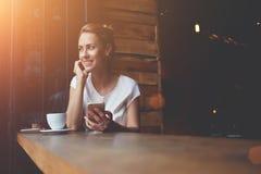 使用手机的愉快的欧洲女性,当放松在现代咖啡店在工作天以后时 免版税库存图片