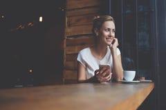 使用手机的愉快的欧洲女性,当放松在现代咖啡店在工作天以后时 库存照片