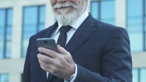 使用手机的愉快的资深商人,读关于成功的成交的消息 影视素材