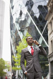 使用手机的愉快的非裔美国人的商人在大厦之外 图库摄影