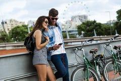 使用手机的愉快的年轻夫妇在街道 库存照片