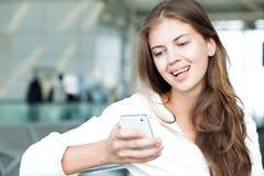 使用手机的愉快的年轻长发妇女 免版税库存照片
