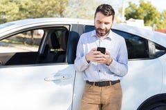 使用手机的所有者反对白色汽车 免版税库存照片