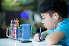 使用手机的男孩和在家绘在白皮书 免版税库存图片