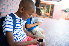 使用手机的男小学生在走廊在学校 库存图片