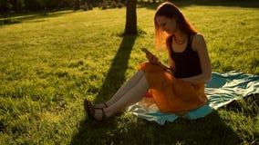 使用手机的红发女性在夏天公园 股票视频