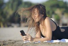 使用手机的美丽和愉快的亚裔妇女发短信在放松的互联网社会媒介微笑 免版税库存照片