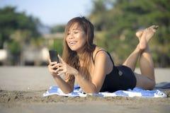 使用手机的美丽和愉快的亚裔妇女发短信在放松的互联网社会媒介微笑 库存照片