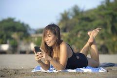 使用手机的美丽和愉快的亚裔妇女发短信在放松的互联网社会媒介微笑 库存图片