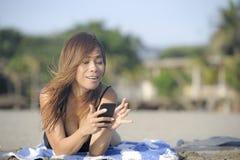 使用手机的美丽和愉快的亚裔妇女发短信在放松的互联网社会媒介微笑 免版税库存图片